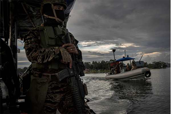 Navy Special Forces patrolling a lake near the main battle area in Marawi in September. Credit Jes Aznar for The New York Times