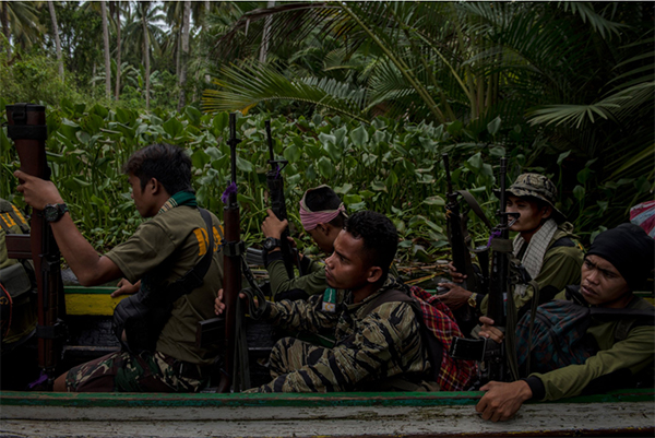Moro Islamic Liberation Front fighters traversing a swamp to fight Islamic State-inspired militants in Datu Salibo. Credit Jes Aznar for The New York Times
